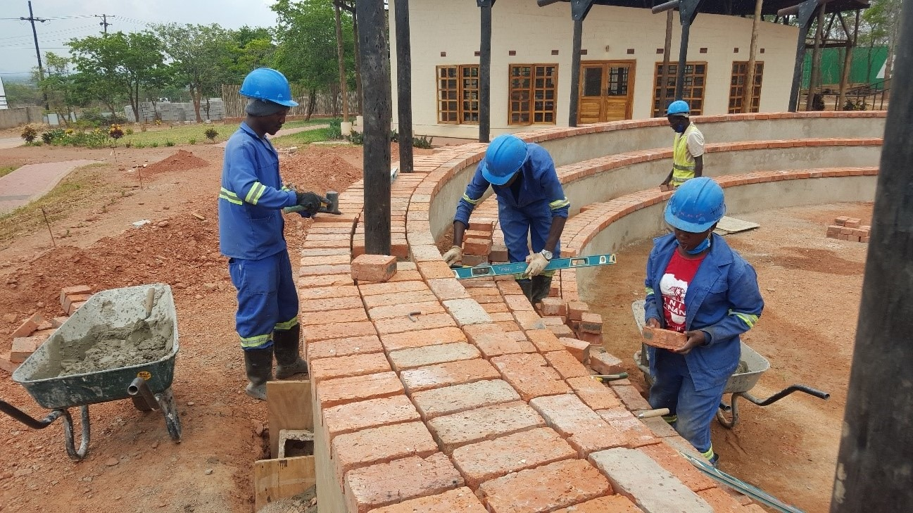 Trainees laying pavers on the seating area of the roundabout