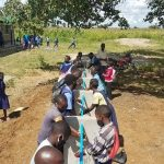 Pupils washing their hands at the new hand wash station at Mukuyu Community School