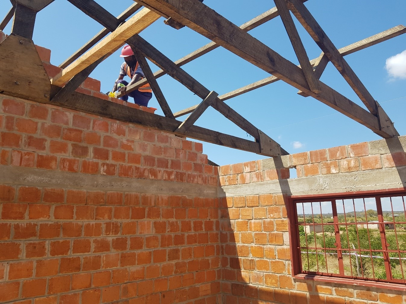 Fixing the purlins on the new classrooms at Light of Hope Community School