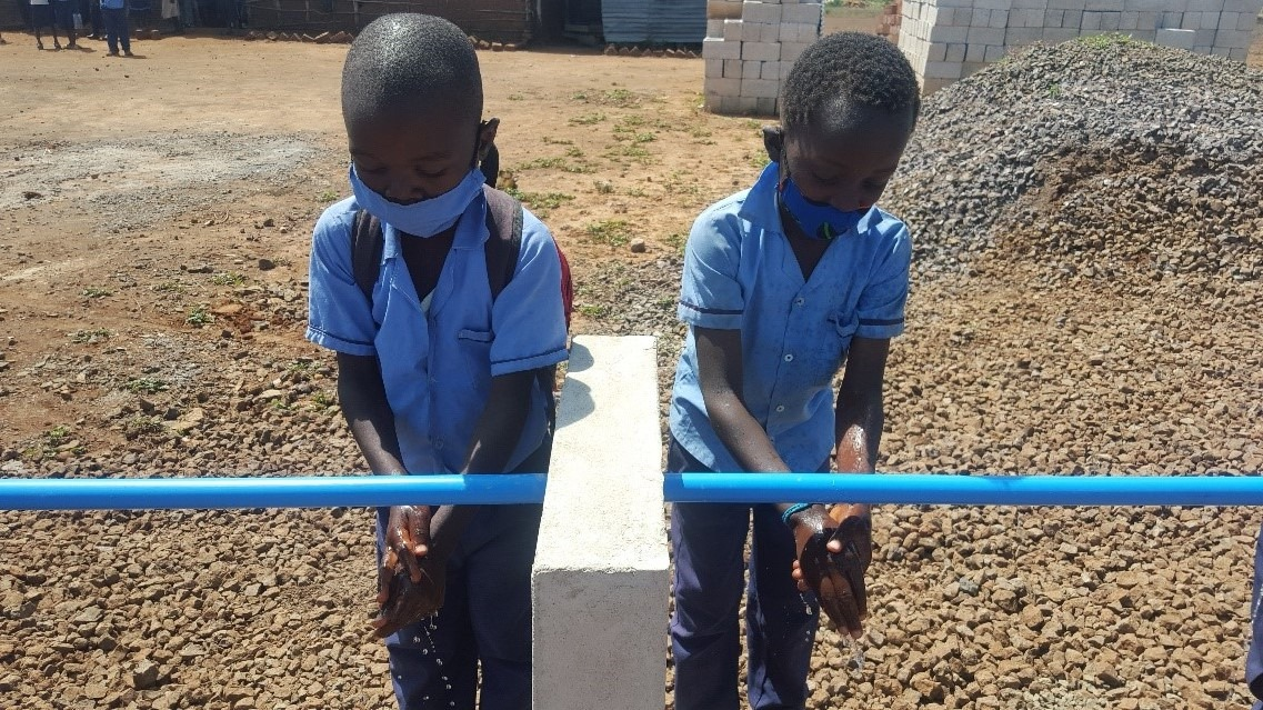 Grade Two pupils washing hands at the new station at Light of Hope Community School