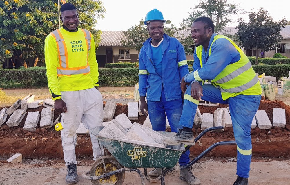 Graduates William Elliot and Justin building hand wash stations through the Safe Hands initiative